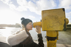 Side view of young woman in hooded sweatshirt looking through telescope by river Thames, London, UK Stock Image