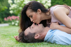 Side view of young woman kissing man while lying in park. Side view of young women kissing men while lying in park stock photos