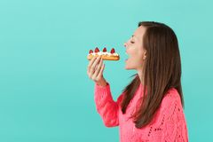 Side view of young woman in knitted pink sweater with closed eyes hold in hand, eating eclair cake isolated on blue. E view of young woman in knitted pink stock image