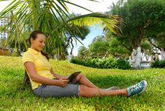 Side view of young woman on the lawn with her tablet computer Royalty Free Stock Photography
