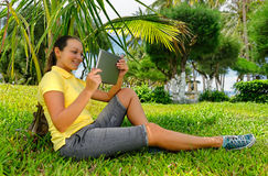 Side view of young woman on the lawn with her tablet computer Stock Photos