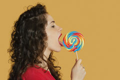 Side view of a young woman licking lollipop over colored background Stock Images