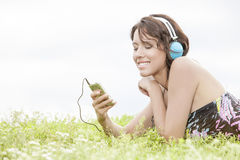 Side view of young woman listening to music through cell phone using headphones while lying on grass against clear sky Royalty Free Stock Photos