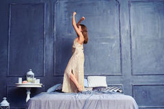 Side view of a young woman in a long nightgown dancing on the be. Side view shot of a young female dancing on the bed early in the morning. Good-looking brunette Stock Image