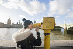 Side view of young woman looking through telescope by river Thames, London, UK Stock Photos