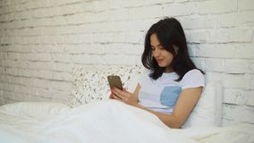 Side view of young woman lying in bed and video chatting using her smartphone.  stock video footage