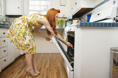 Side view of young woman opening oven door Stock Image