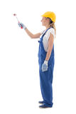 Side view of young woman painter in blue builder uniform with pa Royalty Free Stock Photography