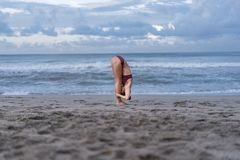 side view of young woman practicing yoga in Standing Forward Bend pose (Uttanasana) on seashore stock photography