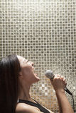 Side view of young woman singing into a microphone at karaoke, shiny background Royalty Free Stock Photography