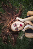 Side view of young woman sleeping on grass at park Royalty Free Stock Photo