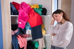 Woman Sleeping Near Messy Clothes On Shelf. Side View Of A Young Woman Sleeping Near Messy Clothes On Shelf stock images