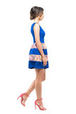 Side view of young woman in summer sleeveless blue short dress walking looking ahead. Full body length portrait isolated on white studio background Royalty Free Stock Photos