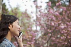 Side view of young woman talking on the phone outdoors in the park in springtime Royalty Free Stock Images