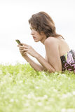 Side view of young woman text messaging through cell phone while lying on grass against clear sky Royalty Free Stock Images