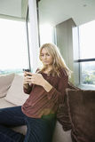 Side view of young woman text messaging at home Royalty Free Stock Images