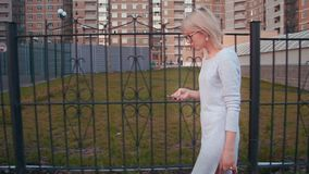 Side view of a young woman walking in the city using smartphone texting and using app. Stock footage of a Side view of a young woman walking in the city using stock footage