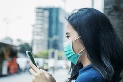 Woman with mask and smartphone at outdoors royalty free stock photos