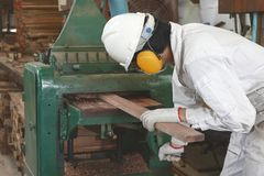 Side view of young wood worker in white safety uniform working with planing machine in factory. Stock Photos