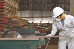 Side view of young worker in uniform and safety equipment cutting a piece of wood on table saw machine in carpentry factory. Side view of young worker in Royalty Free Stock Photo
