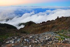 Side of volcano caldera. Rugged, barren side of a volcano caldera in the Canaries Islands with nearby clouds Stock Image