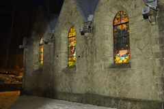 Side wall of a stone church with stained-glass windows. By night Stock Photography