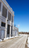 Side of white brick industrial building on sunny winter day Stock Image