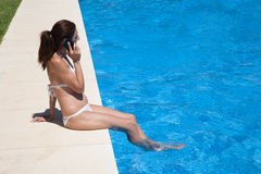 Side woman sitting on edge of pool talking on the phone Royalty Free Stock Photos