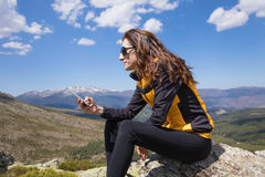 Side woman typing mobile on top of mountain Stock Images