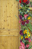 Side of wood door decorated with flowers Royalty Free Stock Photo