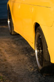 Side of a yellow automobile. A closeup of the side of a yellow car, with custom black rims Stock Image