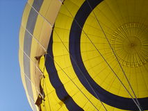 Side of yellow hot air balloon with blue sky. View of a side of yellow hot air balloon with blue sky Royalty Free Stock Image