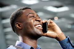 Side of young african american man talking on cellphone and laughing. Side portrait of young african american man talking on cellphone and laughing stock image