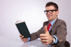 Side of young business man with book showing thumb up Stock Image
