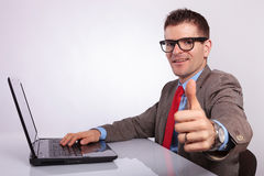 Side of young business man at laptop, showing thumb up Stock Images