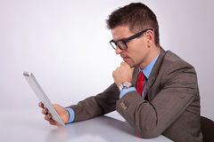 Side of young business man looking pensively at his tablet Stock Photo