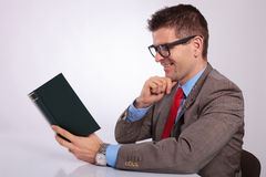 Side of young business man reading a book with hand on chin Royalty Free Stock Image