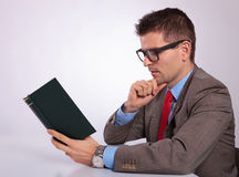 Side of young business man reading a book pensively Stock Image