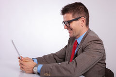 Side of young business man smiling at his tablet. Side view picture of a young business man holding a tablet and smiling while reading from it. on a gray Stock Photo