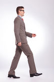 Side of young business man walking straight forward Stock Photography