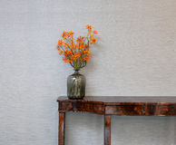 Sideboard in front of a grey wall with flower vase Stock Image