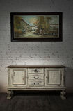 Sideboard and  hanged painting over wooden floor and bricks wall Stock Images