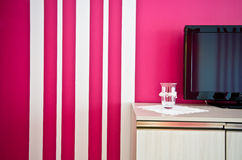 Sideboard with TV and red striped wall Royalty Free Stock Photography