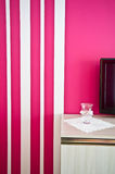 Sideboard with TV and red striped wall Stock Photography