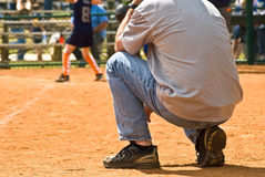 Sideline Coach/Girls Softball. A man on the sidelines at a girls softball game watching the batter and ready to tell the runners what to do Stock Photos