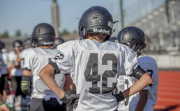 Sidelined Football Players. A group of high school football players on the sideline stock photo