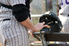 On the sidelines. Baseball player awaits his turn on the sidelines Stock Photo