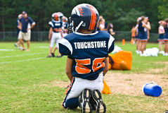 On the Sidelines / Little League. A young football player on the sidelines watching the action on the field Royalty Free Stock Photos