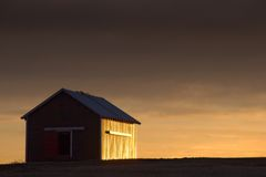 Sidelit Barn. Warm light reflects off the side of an aging barn at sunset stock photography