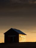 Sidelit Barn. Warm light reflects off the side of an aging barn stock photos